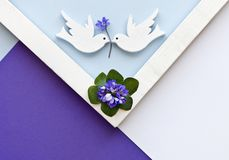 Grußkarte mit blauen Blumen und zwei weißen Tauben auf dem bunten Papierhintergrund Geometrisches Muster des Blumenebenenlage-Min Lizenzfreies Stockfoto