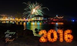 Grußkarte mit bokeh Stellen 2016, bunte Feuerwerke am Pier nachts, Reflexion im Wasser und Schattenbilder von Steinen in FO Lizenzfreies Stockbild