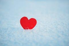 Grußkarte mit einsamem Herzen auf dem blauen Schnee der Blendung Lizenzfreie Stockbilder