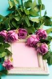 Grußkarte mit schönem hölzernem WeinleseBilderrahmen, frischen rosa Rosen und Kopienraum Stockbilder