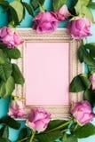 Grußkarte mit schönem hölzernem WeinleseBilderrahmen, frischen rosa Rosen und Kopienraum Lizenzfreie Stockfotografie