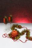 Grußkartenschablone gemacht vom goldenen und grünen Lametta mit roten Weihnachtsbällen, rotem Band, orange Kerze und zwei Gläsern Lizenzfreie Stockfotografie