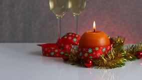 Grußkartenschablone gemacht vom goldenen und grünen Lametta mit roten Weihnachtsbällen, rotem Band, orange Kerze und zwei Gläsern Lizenzfreies Stockbild