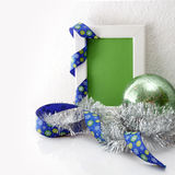 Grußkartenschablone gemacht vom weißen Rahmen und von der Green Card mit blauem Band, grünem Ball und Silberlametta Stockbild