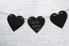 Grußkartenvalentinsgruß Drei Herzen hängen an einem Seil, auf einer Ziegelsteinlichtwand stockbilder