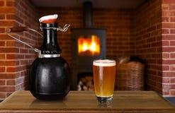 Gruñidor y vidrio de cerveza en casa imágenes de archivo libres de regalías