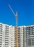 Gru alte ed alloggio multistorey in costruzione Immagine Stock