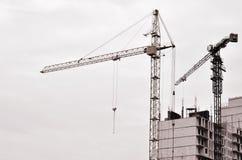 Gru alte funzionanti dentro il posto per con gli edifici alti in costruzione contro un chiaro cielo blu Funzionamento della costr Immagini Stock