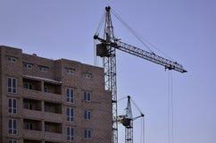 Gru alte funzionanti dentro il posto per con gli edifici alti in costruzione contro un chiaro cielo blu Funzionamento della costr Fotografie Stock Libere da Diritti
