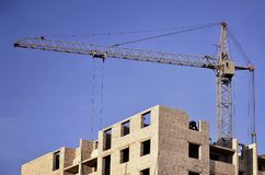 Gru alte funzionanti dentro il posto per con gli edifici alti in costruzione contro un chiaro cielo blu Funzionamento della costr Immagini Stock Libere da Diritti