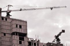 Gru alte funzionanti dentro il posto per con gli edifici alti in costruzione contro un chiaro cielo blu Funzionamento della costr Immagine Stock