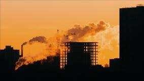 Gru del cantiere su costruzione nella siluetta retroilluminata di ora dorata della citt?, di alba o di tramonto stock footage