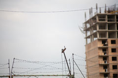 Gru della costruzione ai precedenti di una costruzione multipiana in costruzione Immagini Stock