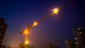 Gru della costruzione che funziona alla notte Fotografia Stock