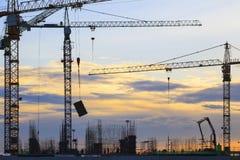 Gru della costruzione di edifici contro il bello cielo oscuro fotografia stock
