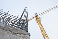 Gru di costruzione contro il cielo blu Mattoni che si situano all'aperto Alta costruzione di aumento che va in su immagine stock