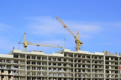 Gru di costruzione e una struttura della casa su un cielo blu immagine stock