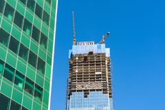 Gru di costruzione sul condominio del grattacielo della costruzione, su un fondo di struttura di vetro delle finestre finanziarie Fotografia Stock