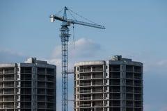 Gru e casa di costruzione in costruzione contro il cielo immagine stock libera da diritti