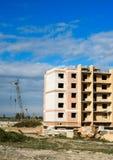 Gru e condominio della costruzione in costruzione contro il cielo Immagini Stock