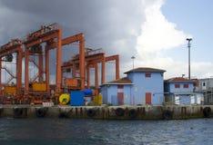 Gru e contenitori del porto marittimo con il cielo cloudly scuro fotografie stock libere da diritti