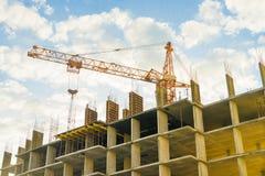 Gru e costruzione in costruzione contro un cielo nuvoloso fotografia stock libera da diritti