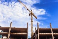 Gru e lavoratori al cantiere contro cielo blu immagine stock