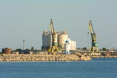 Gru e silo industriali in porto Immagini Stock