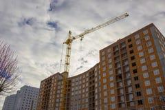 Gru e sito della costruzione di edifici contro cielo blu Immagini Stock Libere da Diritti