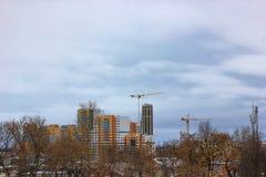 Gru e sito della costruzione di edifici contro cielo blu Immagine Stock
