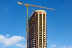 Gru e sito della costruzione di edifici contro cielo blu Fotografia Stock