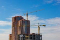 Gru e sito della costruzione di edifici contro cielo blu Fotografia Stock Libera da Diritti