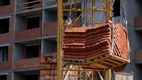 Gru e sito della costruzione di edifici contro cielo blu onere gravoso che appende sul gancio di una gru sulla costruzione di Fotografia Stock Libera da Diritti