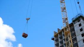 Gru e sito della costruzione di edifici contro cielo blu onere gravoso che appende sul gancio di una gru sulla costruzione di Fotografia Stock