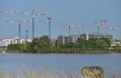 Gru e sito di costruzione contro un cielo blu immagini stock