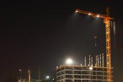 Gru gialle alte con illuminazione e costruzione Immagini Stock Libere da Diritti