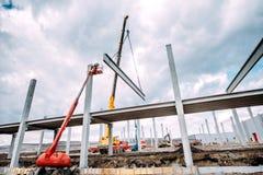 Gru industriale resistente che funziona sul cantiere, corridoio concreto di costruzione con i fasci prefabbricati fotografie stock libere da diritti