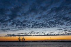 Gru industriali in un porto al tramonto immagini stock