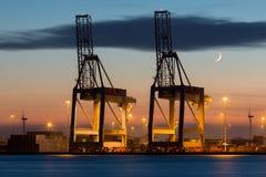 Gru industriali in un porto al tramonto immagini stock libere da diritti