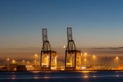 Gru industriali in un porto al tramonto immagine stock