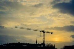 Gru sulla città anonima nel tramonto immagini stock libere da diritti