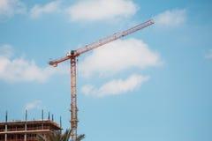 Gru a torre nel cantiere sopra cielo blu con le nuvole Immagini Stock
