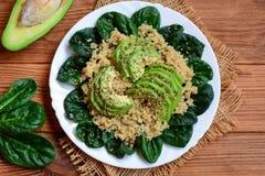Gruau épicé de quinoa Quinoa de Vegan avec de la salade d'épinards et d'avocat d'un plat blanc Table en bois de Brown Type rustiq Photos libres de droits