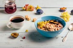 Gruau avec la prune fraîche, les raisins verts et la tasse de café photos stock