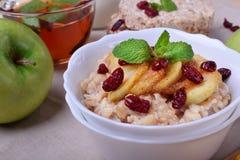 Gruau avec les pommes caramélisées et les canneberges sèches complétées avec la menthe photographie stock libre de droits