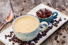 Gruau de farine d'avoine avec du café et le chocolat râpé sur la table en bois lumineuse photo libre de droits