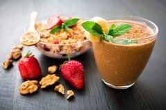 Gruau de farine d'avoine avec le smoothie de banane de myrtilles, de fraises, de muesli et de chocolat sur la table en bois Petit Photos libres de droits