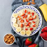 Gruau de farine d'avoine avec les fraises, la banane et les amandes r photo libre de droits