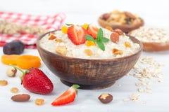 Gruau de farine d'avoine dans la cuvette avec les fraises, les écrous et les fruits secs frais Photographie stock