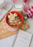 Gruau de farine d'avoine de petit déjeuner avec des bananes, des graines, des écrous et le lait Image stock